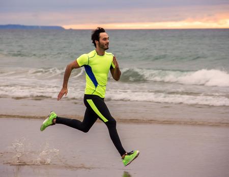 Runner man training on the beach Imagens