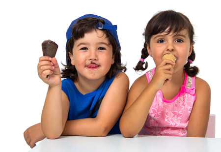 Little boy and girl eating an ice cream isolated on white photo