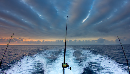 atún: Cañas de pescar en barco más de un hermoso paisaje marino nublado Foto de archivo