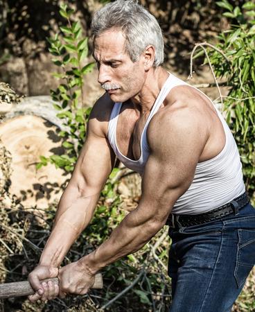 leñador: Leñador musculoso veterano en el trabajo