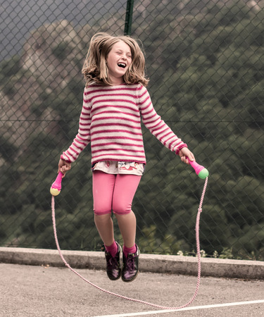 Portrait of a little girl jumping rope photo