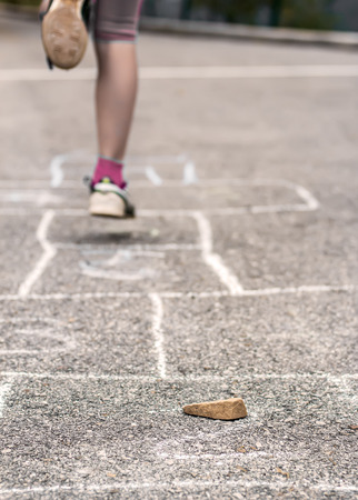 Litlle girl playing on the hopscotch Imagens