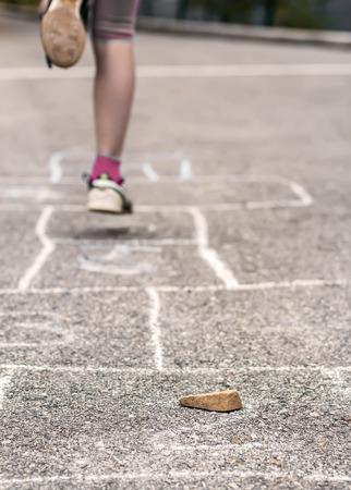 Muchacha de Litlle que juega en la rayuela