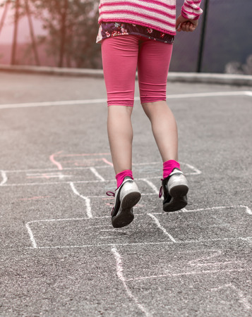 Litlle girl playing on the hopscotch Stock Photo