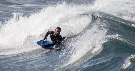 GIJON, SPAIN  Oct, 2014:  Athletes surfing on San Lorenzo beach located in Gijón, in the north of Spain. October 20, 2014