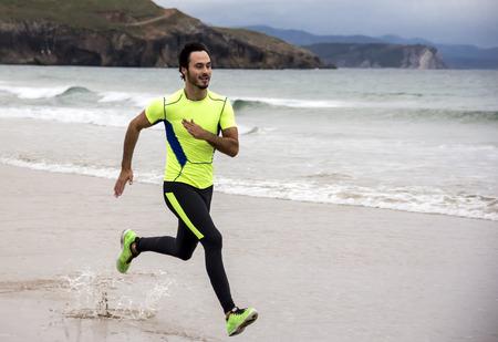 hombre deportista: Entrenamiento del hombre Corredor en la playa