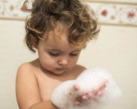 Little girl taking a bath with a foam