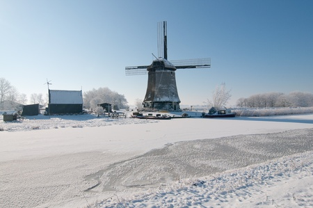 dutch windmill in  snow in clear blue sky Stock Photo - 12336794