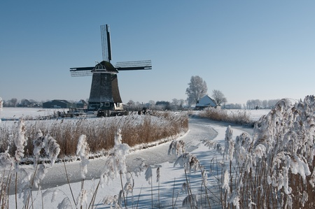 dutch windmill in  snow in clear blue sky photo
