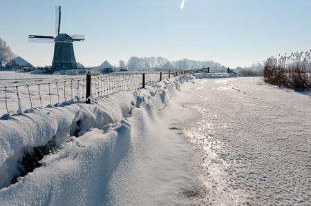 dutch windmill in  snow in clear blue sky