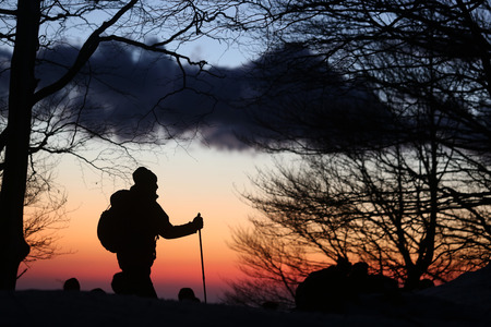snowshoes: hiker walks at sunset with snowshoes