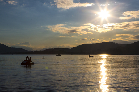 relaxing imagine of people on a  pedalo floating in a placid lake in late evening of summer day 免版税图像