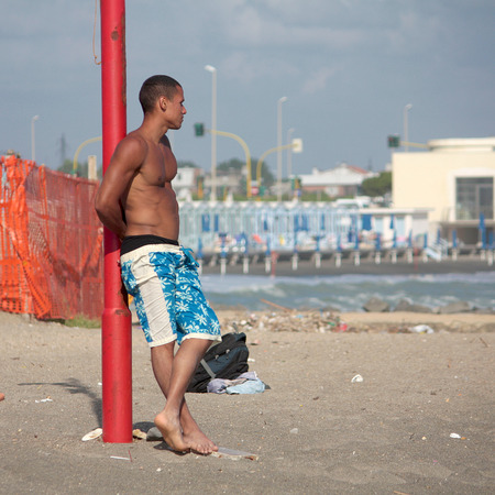 boardshorts: OSTIA, ITALY - JUNE 19, 2010: unidentified young man stands next to a pole in the beach of Ostia. Editorial