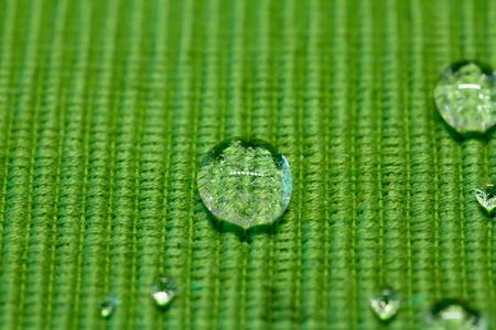 waterproofing material: drops on a green waterproof cloth