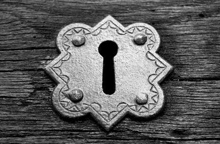 door key: Old Metal Gothic Keyhole on wood in black and white Stock Photo