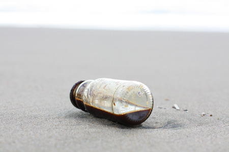 castaway: Coffe Bottle abandoned on the beach Stock Photo