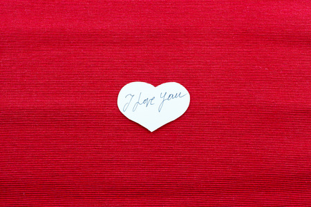 red cloth: I Love you note inside a white paper heart on red cloth Stock Photo
