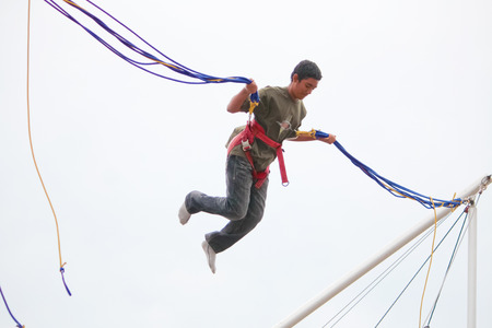 bungee jumping: London, UK - August 15, 2010: unidentified young boy doing bungee jumping at the park.