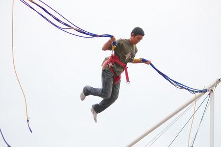 bungee jumping: Londres, Reino Unido - 15 de agosto de 2010: joven no identificado haciendo puenting en el parque. Editorial