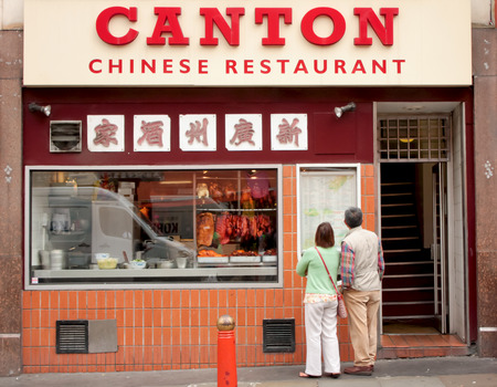 London, Uk - August 17, 2010: unidentified couple of tourists looking for menu prices outside a chinese restaurant in London.