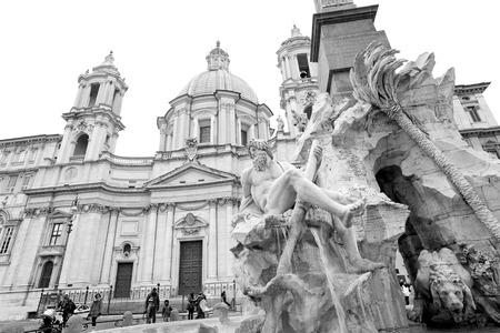 Rome, Italy - January 8, 2017: Fontana dei Fiumi and SantAgnese in Agones facade in Piazza Navona, Rome (Italy). Unidentified tourist enjoing the art of Borromini and Bernini in Rome