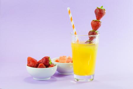 glass of refreshing drink: orange juice with strawberries.