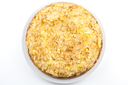 Baked cake with almonds on white background.