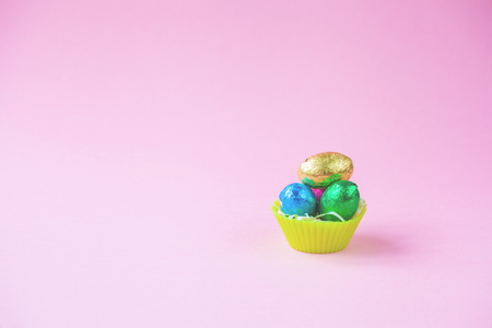 Easter Eggs Chocolates mini basket pink background.