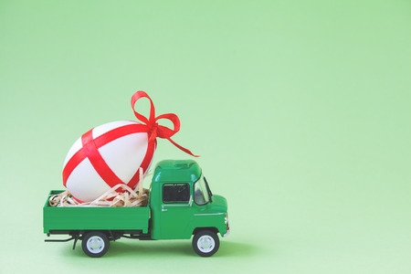 Green pickup toy carrying one decorated easter egg. Foto de archivo