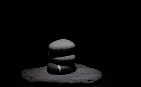 Group of poised stones under a soft light on a black background