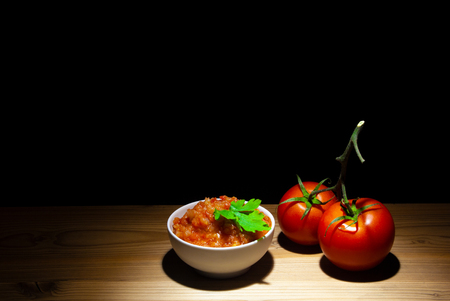 Tomato and Tomato Sauce on wood - black background