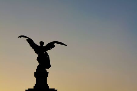 Angel statue silhouette view over Sant Angelo Bridge (Rome , Italy)