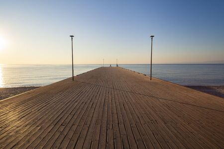 Sea Pier in the early morning with people silhouette (perspective view)