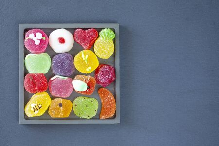 Fruit shaped Jellies in a square tray, top view (slate background)