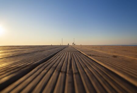 Sea Pier in the early morning with people silhouette (ground framing, perspective view, focus on the background) Фото со стока