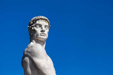 Athlete marble statue portrait against blue sky - sunlight