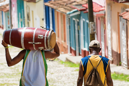 Salsa musician walking and carrying a conga in the streets of Trinidad Cuba