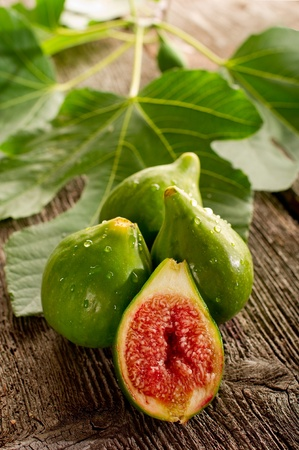 open figs with leaf on wood background photo