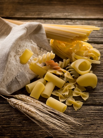 raw pasta with ears and flour on wood background photo