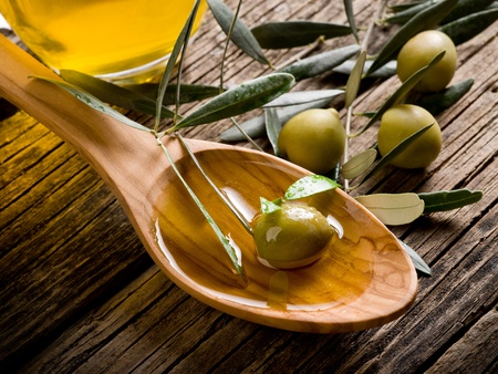 olive oil over wood spoon photo
