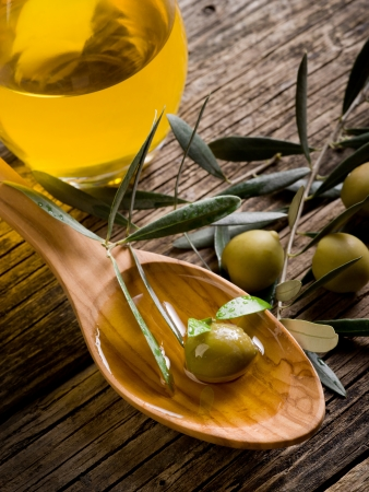 extra virgin olive oil: olive oil over wood spoon
