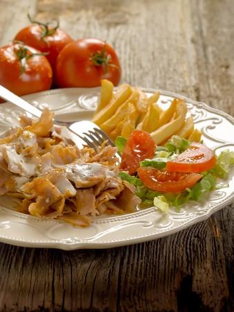pinchos morunos: Kebap con ensalada y patatas en plato Foto de archivo