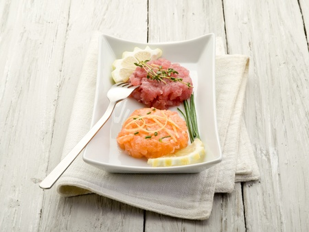 starter: salmon and tuna tartare with lemon and chive Stock Photo