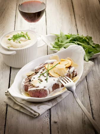 tenderloin with cream sauce ovum mushroom and arugula salad photo