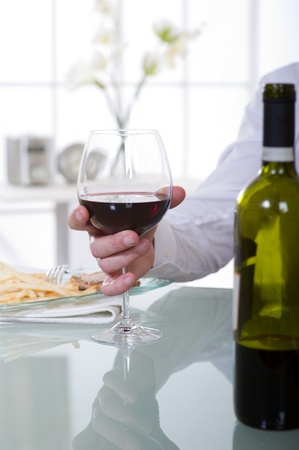 man with glass of red wine at restaurant photo