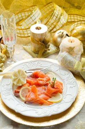 comida de navidad: salmón en un plato en la tabla de Navidad