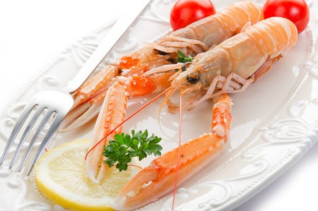 norwey lobster with tomatoes and lemon on dish photo