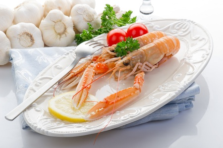 italian foods: norway lobster with tomatoes and lemon on dish
