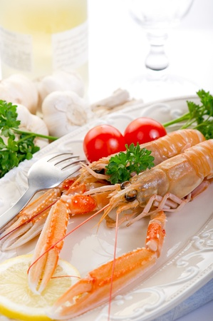 norway lobster with tomatoes and lemon on dish photo