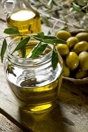 hoja de olivo: aceite de oliva en el fondo de madera